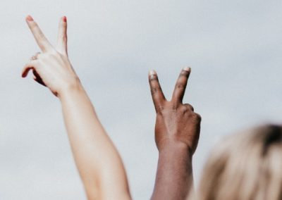 Two hands displaying the peace sign