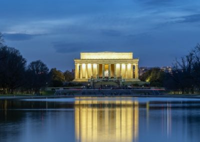 Lincoln Memorial lit up at night with reflection in water