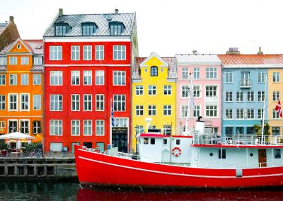 Red boat in front of colorful building in Copenhagen, Denmark