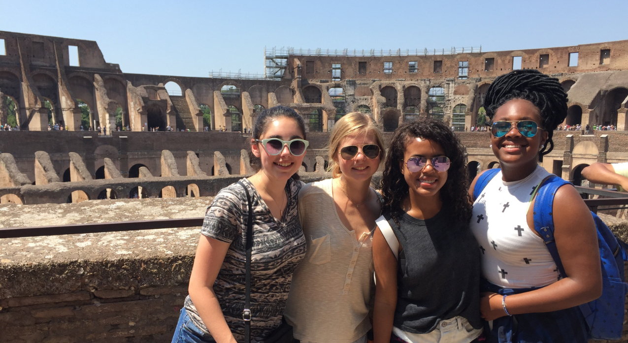 Group of students posing in front of the Colosseum in Rome, Italy