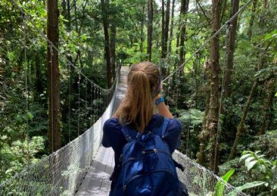 Student with backpack walking across bridge in Costa Rica tropics