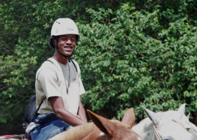 Student smiling at the camera while riding a horse