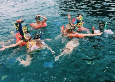 A group of students looking at the camera while in the water with snorkel gear