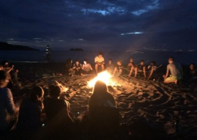 Students around a campfire at night on Costa Rican beach